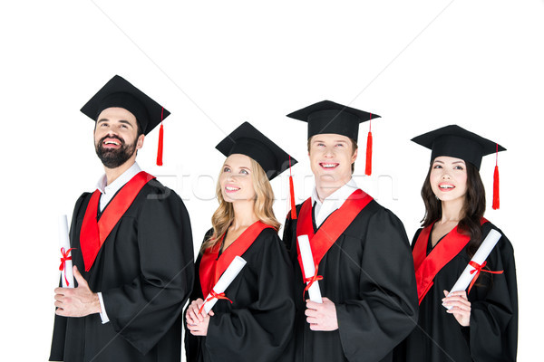 Happy students in graduation gowns and mortarboards holding diplomas on white Stock photo © LightFieldStudios