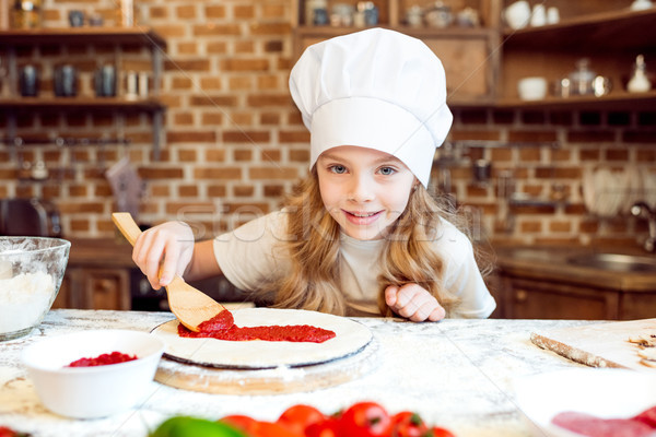 little girl putting tomato sauce on pizza dough Stock photo © LightFieldStudios