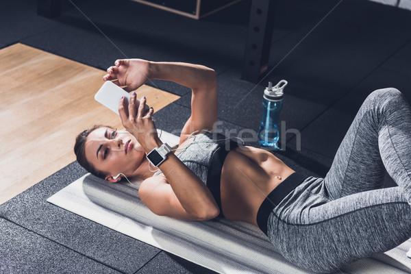 sportive woman using smartphone Stock photo © LightFieldStudios