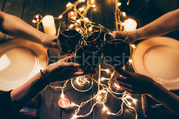 Stock photo: four people clinking glasses with wine