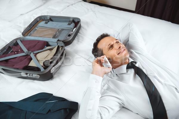 Businessman talking on phone on bed Stock photo © LightFieldStudios