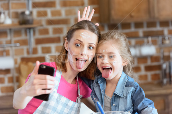 portrait of grimace mother and daughter making selfie while cooking at home Stock photo © LightFieldStudios