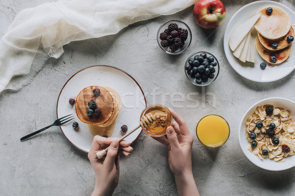 top view of person eating delicious homemade pancakes with honey and fruits on grey Stock photo © LightFieldStudios