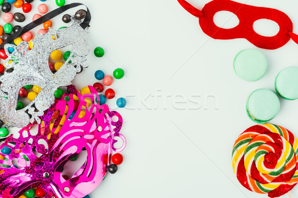 top view of arranged masquerade masks, macarons and candies isolated on grey, purim holiday concept Stock photo © LightFieldStudios