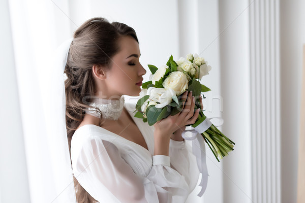 attractive bride in wedding dress and veil sniffing white bouquet Stock photo © LightFieldStudios