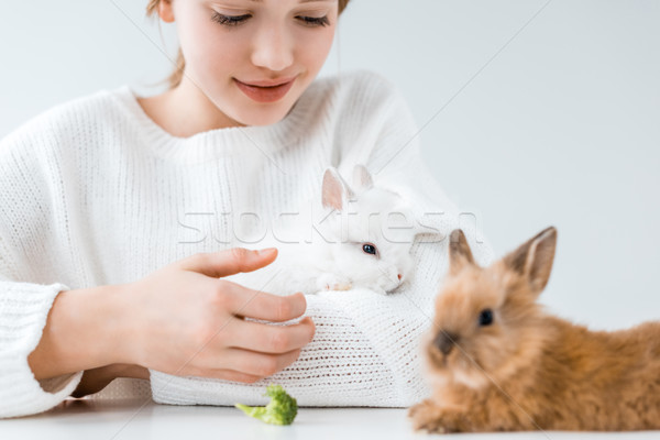 cropped shot of smiling girl feeding rabbits with broccoli on white  Stock photo © LightFieldStudios