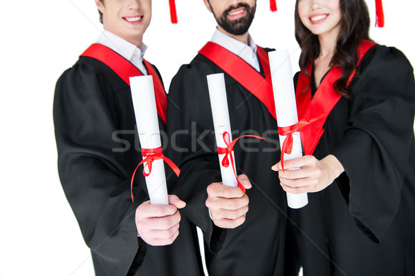 Cropped shot of smiling students in graduation gowns holding diplomas on white Stock photo © LightFieldStudios