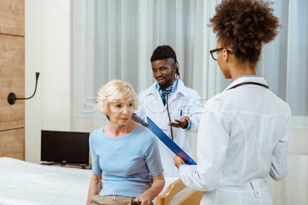 Elderly woman with doctors in hospital Stock photo © LightFieldStudios