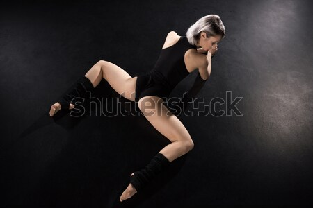 Young athletic woman contemporary dancer posing on black Stock photo © LightFieldStudios