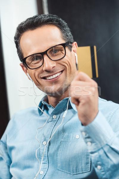 üzletember visel fülhallgató szemüveg tart hitelkártya Stock fotó © LightFieldStudios