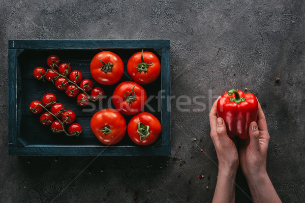 cropped shot of woman holding bell pepper near box of tomatoes on concrete surface Stock photo © LightFieldStudios