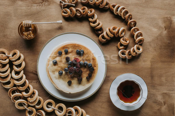 top view of fresh pancakes with berries, cup of tea, honey and bagels on wooden table    Stock photo © LightFieldStudios