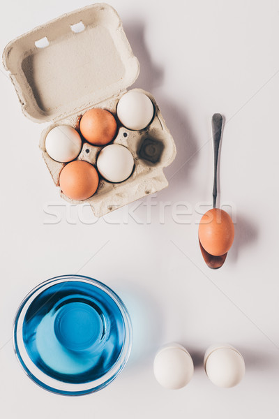 top view of glass with blue paint and chicken eggs on egg tray, easter concept Stock photo © LightFieldStudios