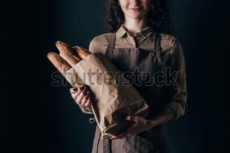 cropped shot of woman in apron holding french baguettes in hands isolated on black Stock photo © LightFieldStudios