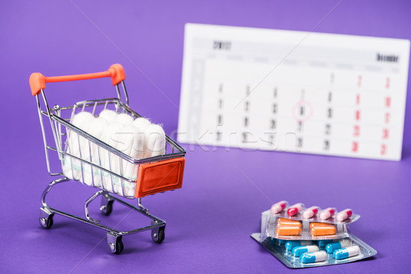tampons in small shopping cart, pills and calendar on purple Stock photo © LightFieldStudios