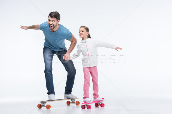smiling father and daughter riding skateboards on white Stock photo © LightFieldStudios
