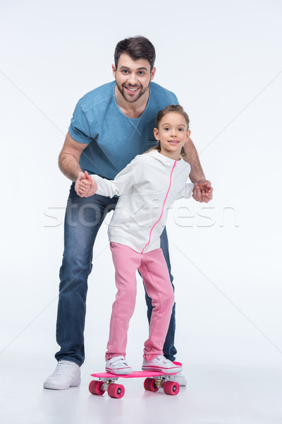 Souriant père aider fille skateboard blanche Photo stock © LightFieldStudios