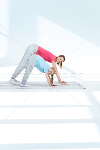 Stock photo: Mother and daughter exercising on yoga mat and smiling at camera