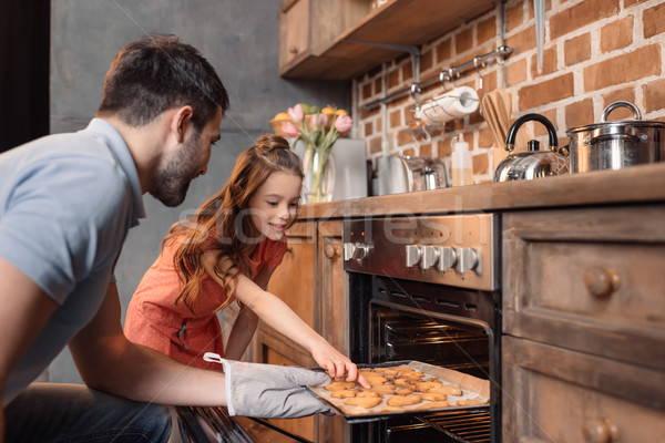 'side view of father and daughter picking cookies out of oven Stock photo © LightFieldStudios