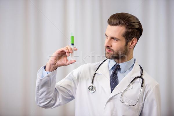 Doctor holding syringe Stock photo © LightFieldStudios