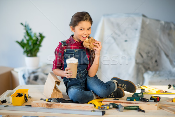 Little girl eating in workshop Stock photo © LightFieldStudios