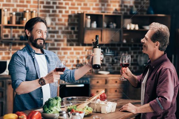 men drinking wine in kitchen Stock photo © LightFieldStudios