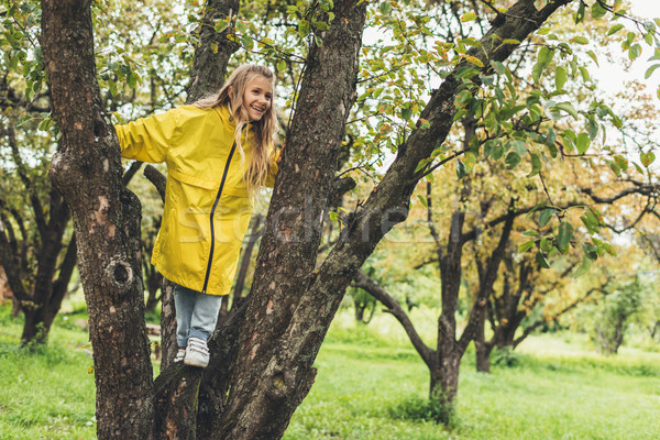 Gyermek esőkabát fa imádnivaló mosolyog citromsárga Stock fotó © LightFieldStudios