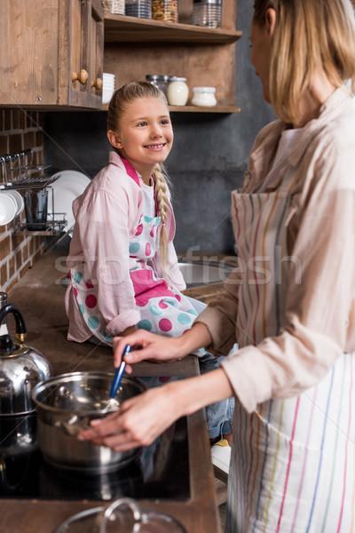 smiling kid watching mother cooking Stock photo © LightFieldStudios