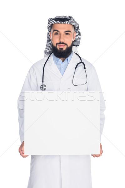 muslim doctor holding blank board Stock photo © LightFieldStudios