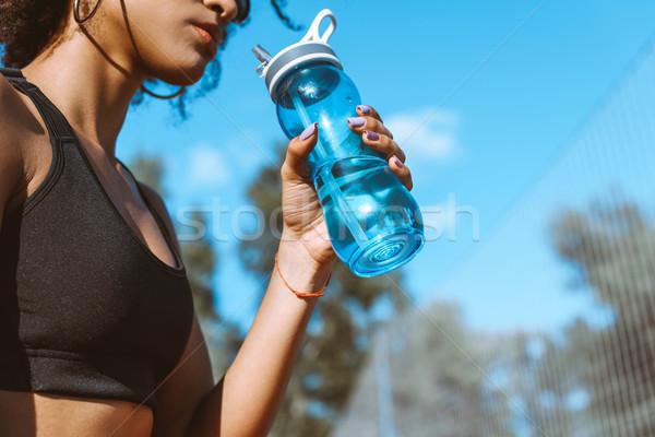 woman drinking from water bottle Stock photo © LightFieldStudios