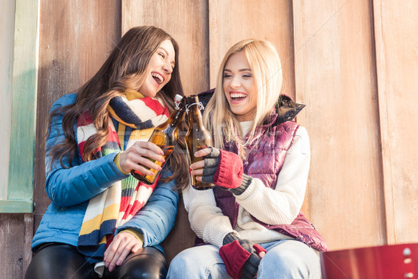 low angle view of laughing women clinking beer bottles on porch Stock photo © LightFieldStudios