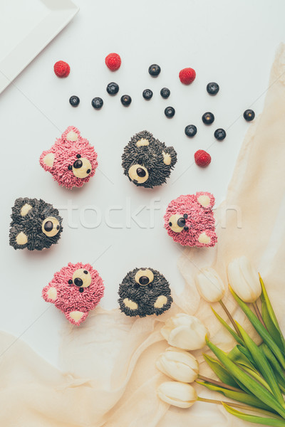 Stock photo: top view of delicious fruity muffins in shape of bears and beautiful tulips