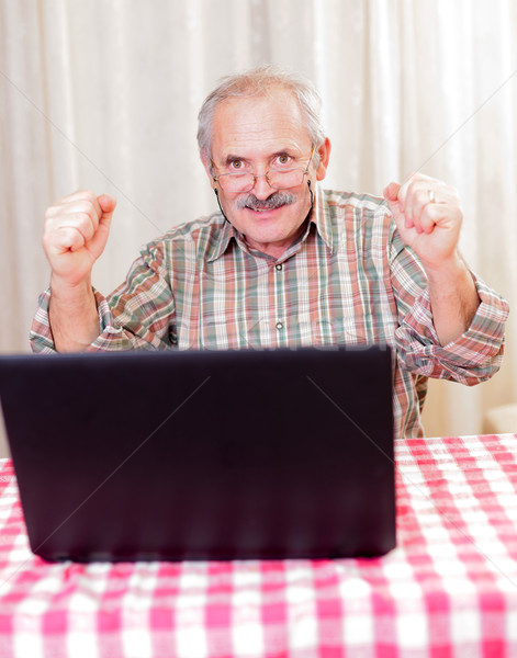 Old man using technology and cheering Stock photo © Lighthunter