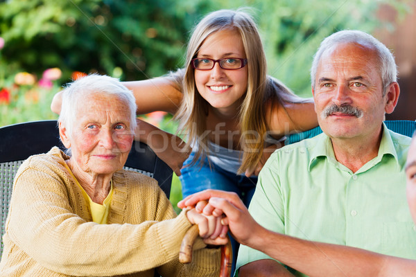 Stock photo: Kind Family Visiting Elderly Lady