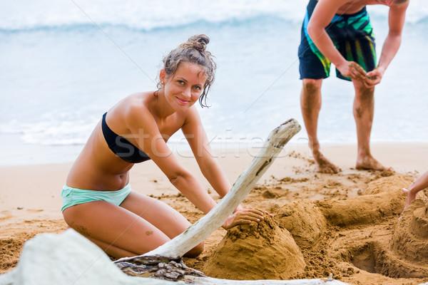 Játszik homok fiatal barna hajú nő tengerpart Stock fotó © Lighthunter