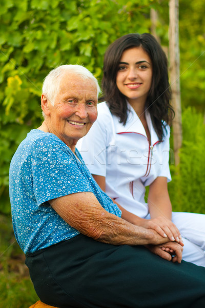 Smiling elderly woman outdoors with doctor / nurse Stock photo © Lighthunter
