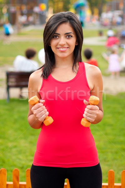 Stock photo: Happy and fit girl working out with barbells