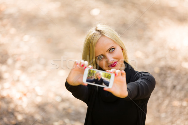 Pretty blond girl taking selfie Stock photo © Lighthunter
