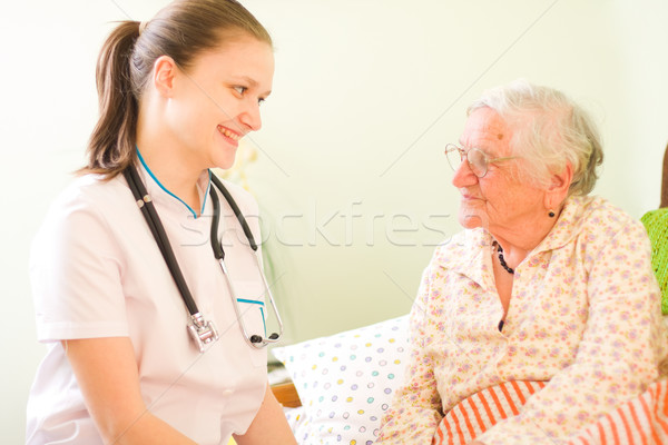 A young doctor / nurse visiting an elderly sick woman socialising - talking - with her. Stock photo © Lighthunter
