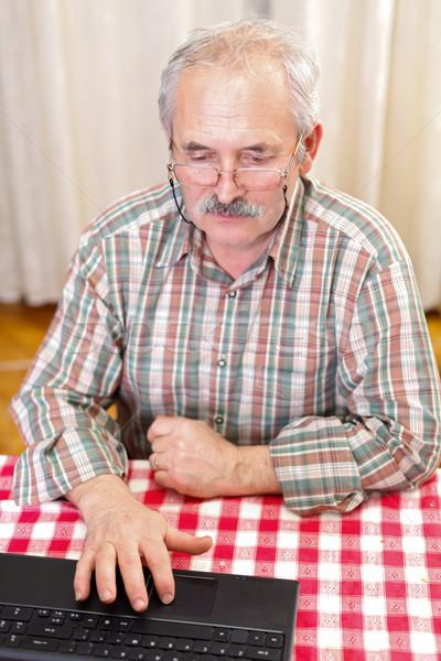 Ancianos hombre tecnología usando la computadora portátil sesión casa Foto stock © Lighthunter