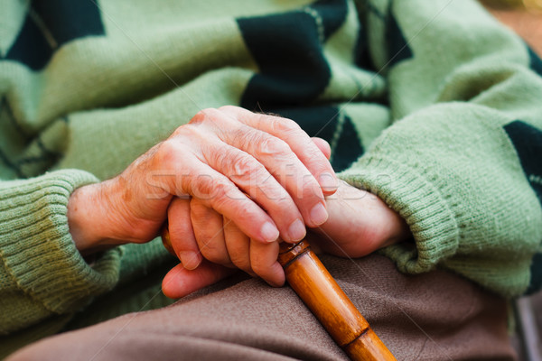 An elderly man sitting, resting his hands on a wooden walking stick. Stock photo © Lighthunter