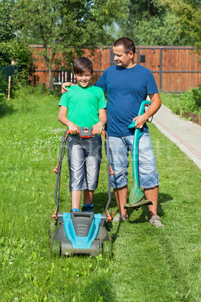 Father and son mowing the lawn Stock photo © lightkeeper