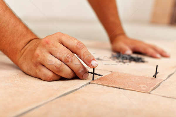 Worker hands placing spacers between ceramic floor tiles Stock photo © lightkeeper