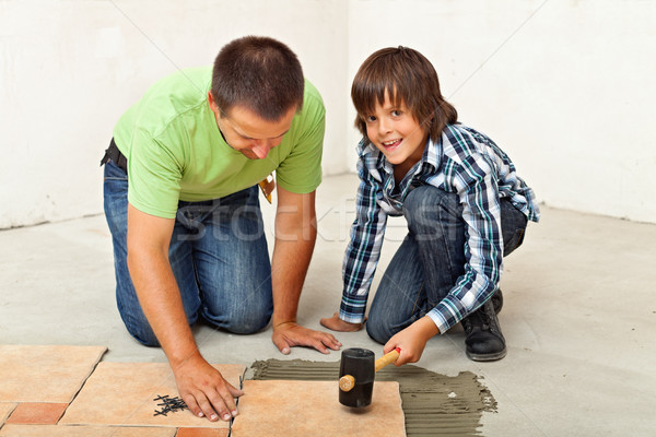 Boy helping his father placing a ceramic floor tile Stock photo © lightkeeper