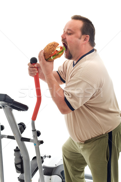 Man eating a large hamburger instead of working out Stock photo © lightkeeper