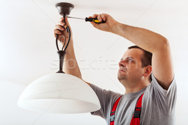 Electrician mounting ceiling lamp Stock photo © lightkeeper