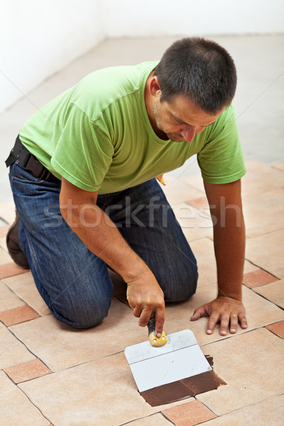 Construction worker testing the joint color on ceramic tiles flo Stock photo © lightkeeper