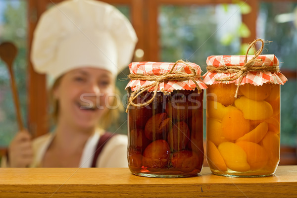 Happy woman chef with homemade canned fruit Stock photo © lightkeeper