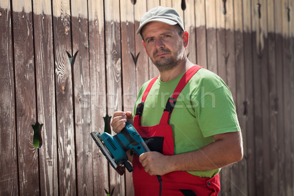Male worker with vibrating sander in front of old wooden fence Stock photo © lightkeeper