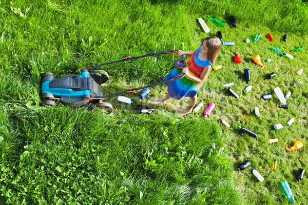 Young girl pushing a lawnmower and leaving plastic litter behind Stock photo © lightkeeper